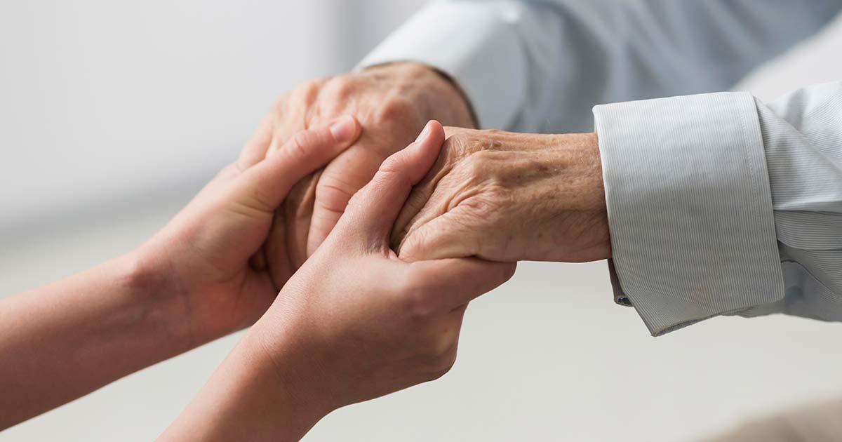 A nurse holding hands of an elderly patient