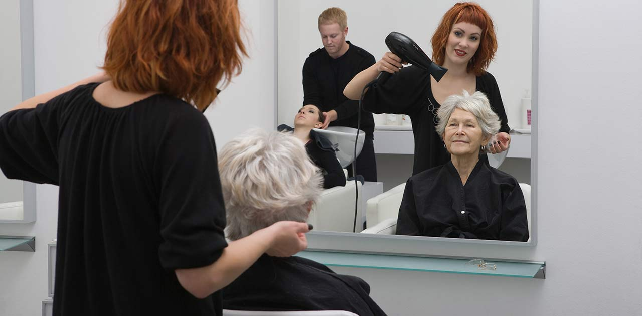 A hair stylist blow drying an older woman's hair