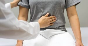 Nurse checking a patient's level of pain in their stomach