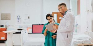 A doctor and nurse communicating a patience chart