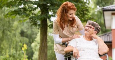 A volunteer nurse helping a woman in a wheel chair