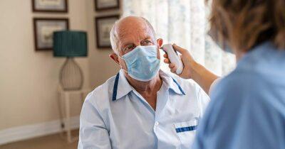 Nurse checking patient's temperature during COVID